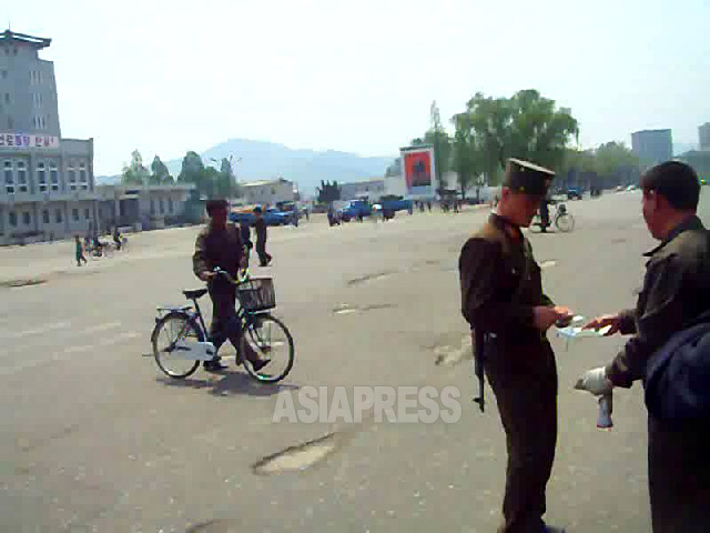 A military policeman checks the identity papers of a pedestrian in Pyongsung City, South Pyongan Province. August 2009. Taken by Kim Dong-cheol (ASIA PRESS)