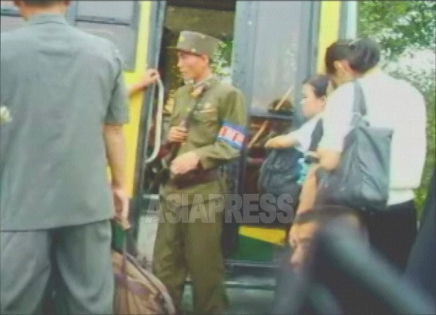 (Reference Photo) A State Security Forces soldier inspects a bus bound for Pyongyang. Taken by Lee Joon.Aug. 2006 (ASIA PRESS)