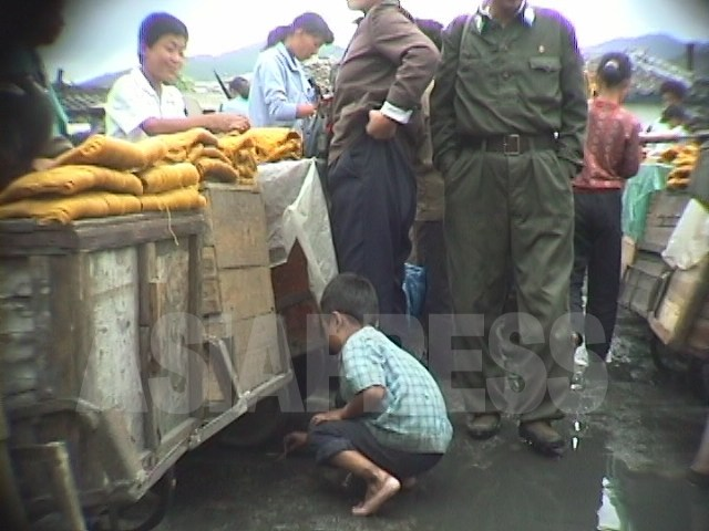 """Children picking up leftover noodles at a black market.  In October 1998, the period called the """"Arduous March,"""" in Wonsan, Kangwon Province.  Taken by Ahn Chol (ASIAPRESS)"""